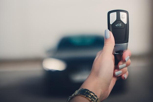 Chiuda sulla mano della chiave dell'automobile della tenuta dell'uomo con l'automobile nera vaga su fondo. Foto Premium