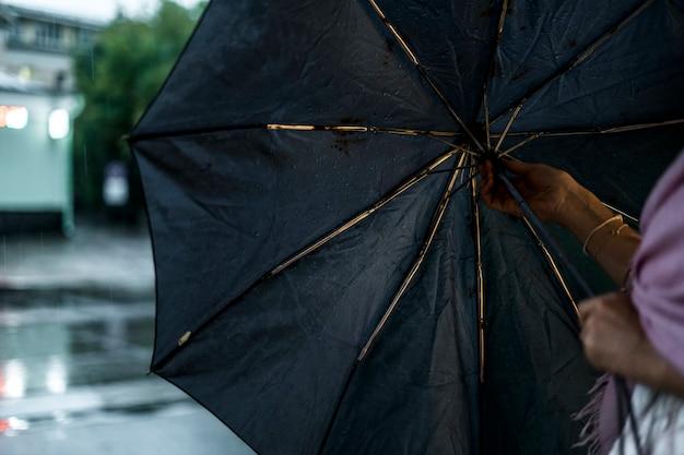 Chiuda sulla mano della donna che apre l'ombrello durante la pioggia nella città Foto Premium