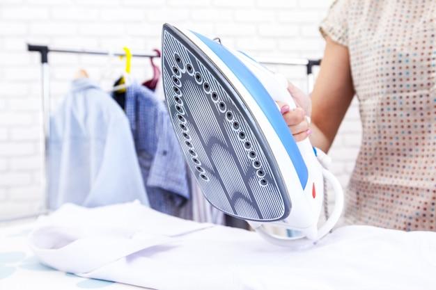 Chiuda sulla mano della donna che riveste di ferro i vestiti sulla tavola Foto Premium