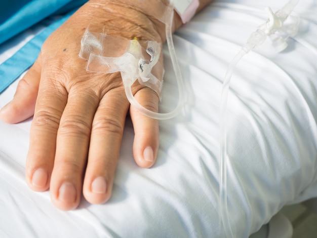 Chiuda sulla mano paziente dell'anziana e l'iv hanno impostato per il gocciolamento salino di goccia endovenosa fluida su bianco Foto Premium