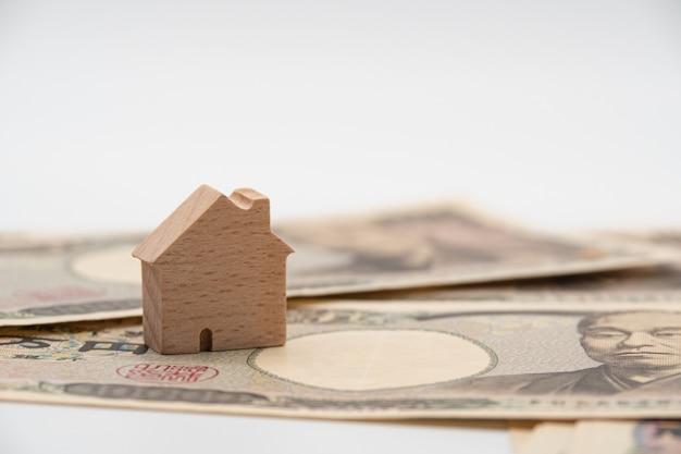 Chiuda sulla piccola casa di legno sulla banconota giapponese dei soldi di yen di valuta. economia del settore immobiliare in giappone. Foto Premium
