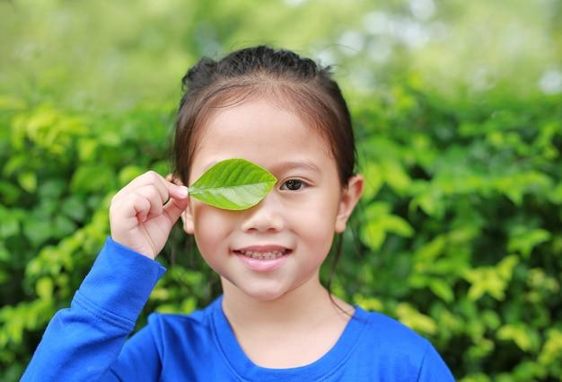 Chiuda sulla piccola ragazza asiatica del bambino che tiene un occhio giusto di chiusura della foglia verde nel fondo verde del giardino. Foto Premium