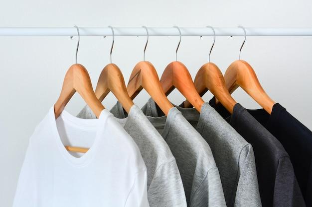 Chiuda sulla raccolta di colore nero, grigio e bianco (monocromatico) che appende sulla gruccia per vestiti di legno nell'armadio o sulla cremagliera dell'abbigliamento Foto Premium