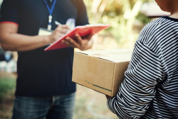 Chiuda sulla scatola della tenuta della donna con la consegna di servizio e tenendo un bordo Foto Gratuite