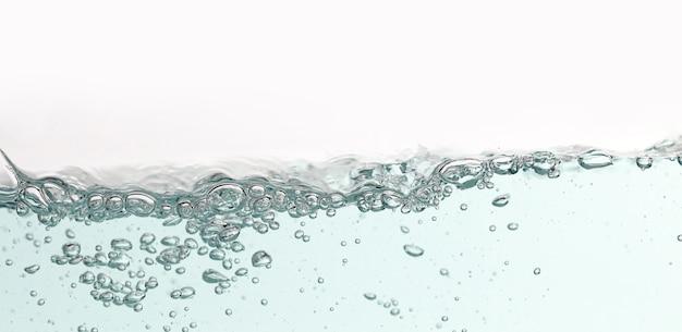 Chiuda sulla spruzzata dell'acqua blu con le bolle di aria. acqua di superficie fresca e pulita che entra nell'onda e nell'acqua pulita isolate. Foto Premium