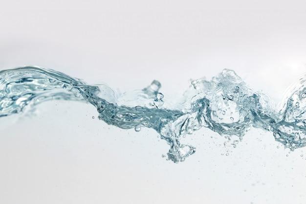 Chiuda sulla spruzzata dell'acqua con le bolle d'aria. acqua di superficie fresca e pulita che entra nell'onda e nell'acqua pulita isolate. Foto Premium