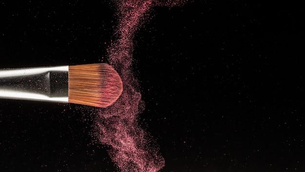 Chiuda sulla spruzzata della polvere e spazzoli per il truccatore o il blogger di bellezza nel fondo nero Foto Premium