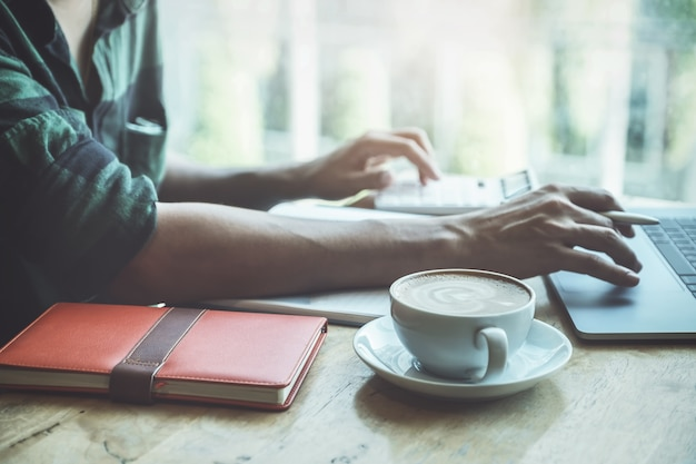 Chiuda sulla tazza di caffè con l'uomo di affari che per mezzo del computer portatile e del calcolatore calculatig per il bilancio di controllo o la finanza della sua società. Foto Premium