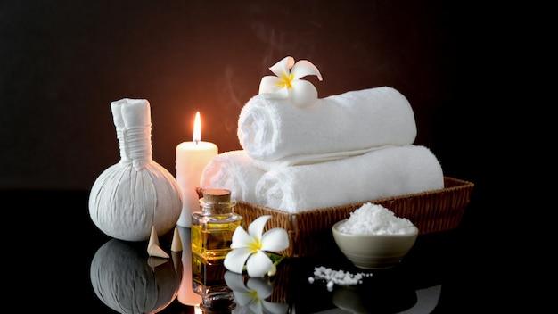 Chiuda sulla vista degli accessori di trattamento della stazione termale con l'asciugamano bianco, la candela e l'olio dell'aroma Foto Premium