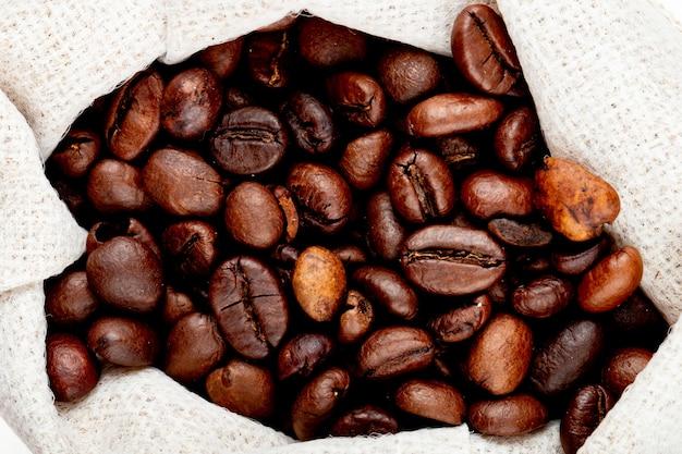 Chiuda sulla vista dei chicchi di caffè marroni in un sacco Foto Gratuite