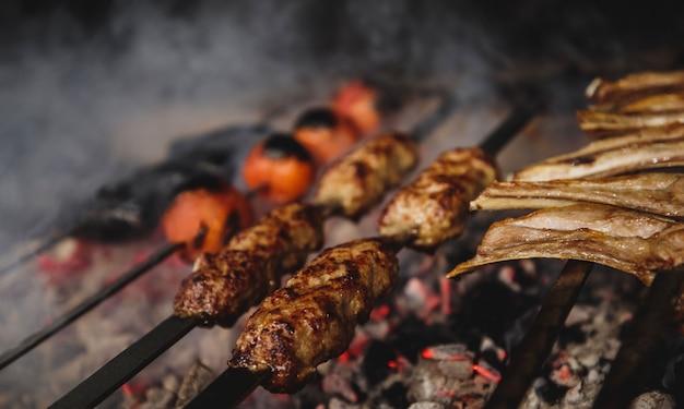 Chiuda sulla vista del kebab di lula sugli spiedi del metallo sulla parete scura Foto Gratuite