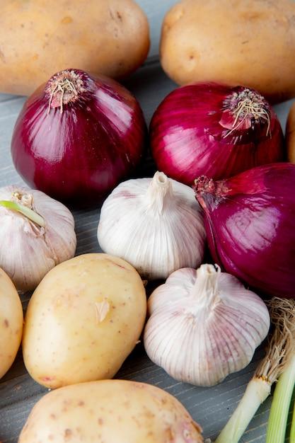 Chiuda sulla vista del modello delle verdure come patata dell'aglio della cipolla rossa su fondo di legno Foto Gratuite