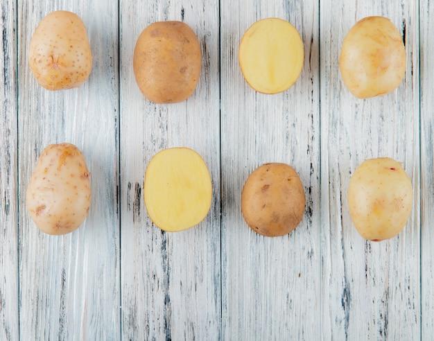 Chiuda sulla vista del modello di patate intere e tagliate su fondo di legno con lo spazio della copia Foto Gratuite