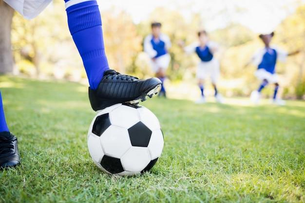 Chiuda sulla vista del pallone sotto le scarpe da calcio contro il gioco dei bambini Foto Premium