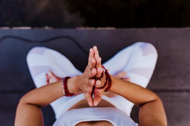 Chiuda sulla vista di giovane donna asiatica irriconoscibile che fa l'yoga in un parco. seduto sul ponte con le mani in preghiera e usando la collana mala. Foto Premium