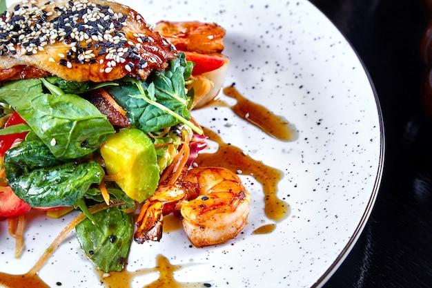 Chiuda sulla vista su insalata calda con gamberetto, avocado, spinaci e salmone sul piatto del wjite. copia spazio per il design. pesce di mare. cibo sano e dietetico. ristorante che serve, pesce alla griglia Foto Premium