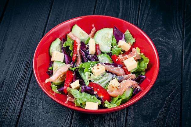 Chiuda sulla vista su insalata fresca fatta in casa con salmone, pomodoro, cetriolo, lattuga e formaggio Foto Premium