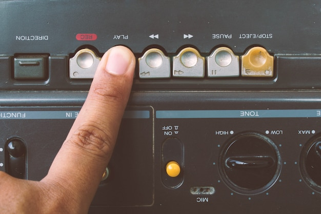 Chiuda sulle dita per giocare il giocatore di cassette radiofonico, stile d'annata. Foto Premium