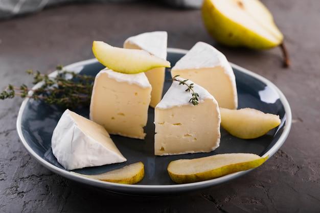 Chiuda sulle fette del camembert con la pera Foto Gratuite