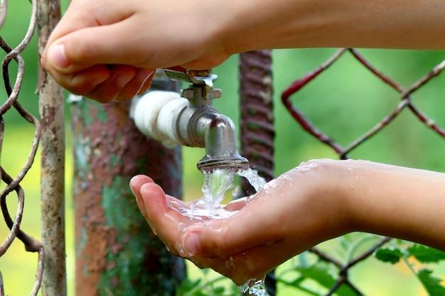 Chiuda sulle mani del bambino con le gocce dell'acqua dal rubinetto d'ottone del vecchio grunge Foto Premium