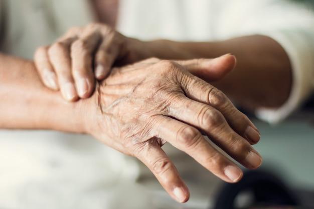 Chiuda sulle mani del paziente anziano della donna anziana che soffre dal sintomo della malattia di pakinson Foto Premium