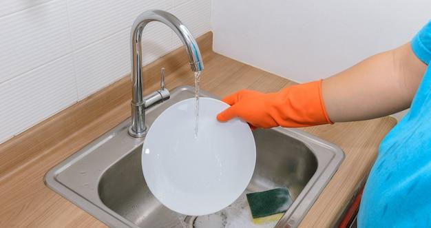 Chiuda sulle mani dell'uomo che lava i piatti Foto Premium