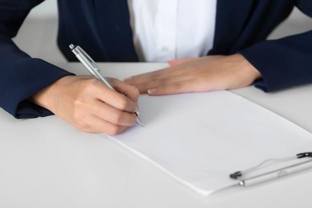 Chiuda sulle mani della donna di affari che indossano un vestito che annota su uno strato della carta in bianco Foto Premium