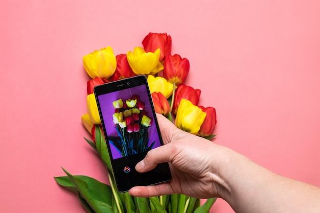 Chiuda sulle mani femminili che prendono la foto di bei fiori con lo smartphone Foto Premium