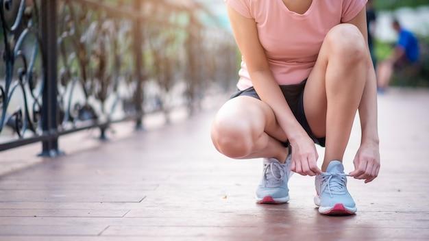 Chiuda sulle scarpe del legame della donna nel parco Foto Premium