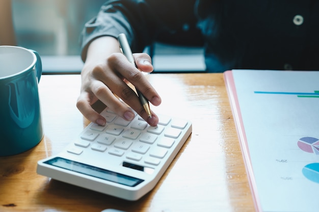 Chiudere un account di lavoro sulla finanziaria con la calcolatrice in ufficio per calcolare le spese, concetto di contabilità. Foto Premium