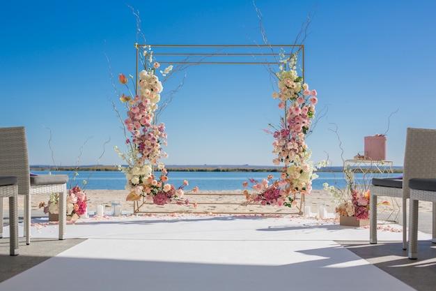 Chuppa di nozze in riva al fiume decorata con fiori freschi. Foto Premium