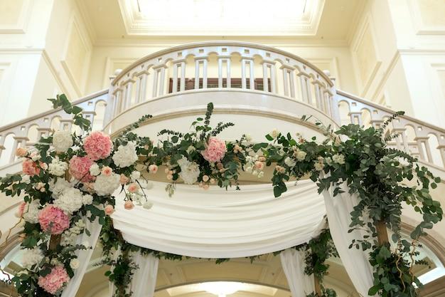 Chuppah di nozze decorato con sala banchetti coperta di fiori freschi di cerimonia nuziale. Foto Premium