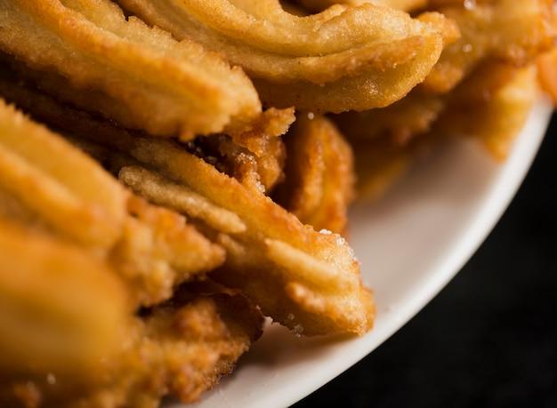 Churros fritti alta vista su un piatto bianco Foto Gratuite