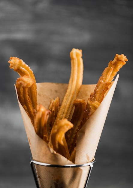 Churros fritti primo piano in una carta da imballaggio Foto Gratuite
