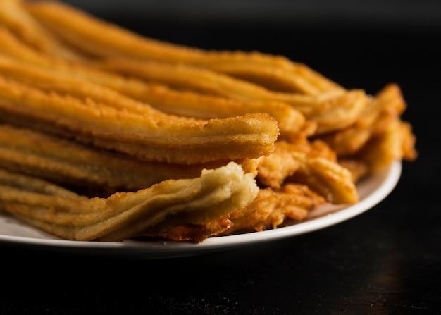 Churros fritti primo piano sul piatto Foto Gratuite