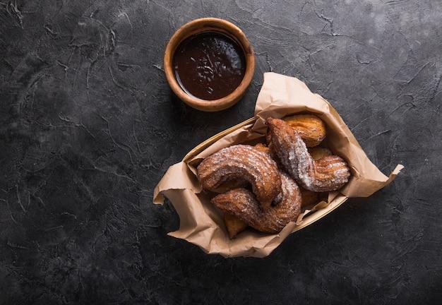 Churros in un sacco di carta con zucchero e salsa di cioccolato sul nero Foto Premium