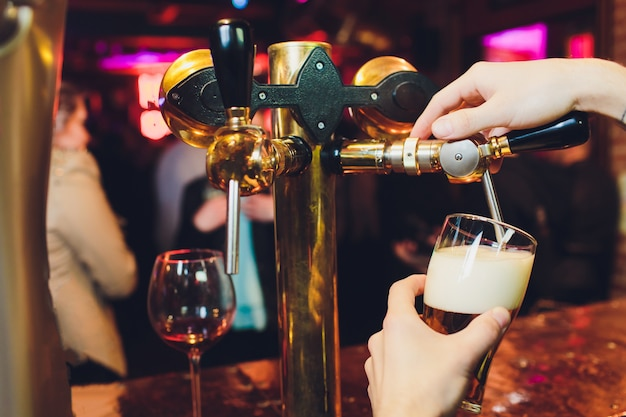 Ci incontriamo all'oktoberfest. mano del barista versando una birra grande birra alla spina Foto Premium