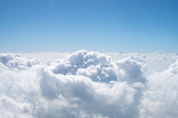 Ci sono molte nuvole bianche tra il cielo blu. questa vista è dalla finestra sull'aereo. Foto Premium