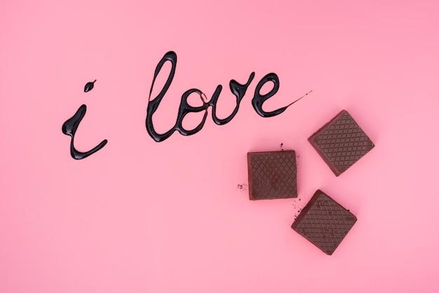 Cialde al cioccolato su sfondo rosa con scritta sciroppo di cioccolato Foto Gratuite