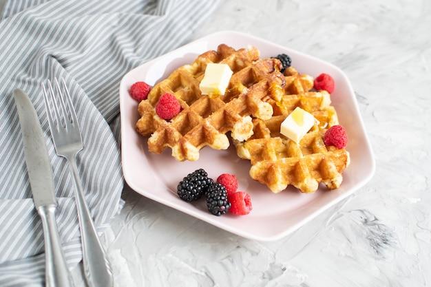 Cialde belghe fatte in casa con burro miele bacche lamponi more tavolo asciugamano da cucina piatto rosa colazione mattutina Foto Premium