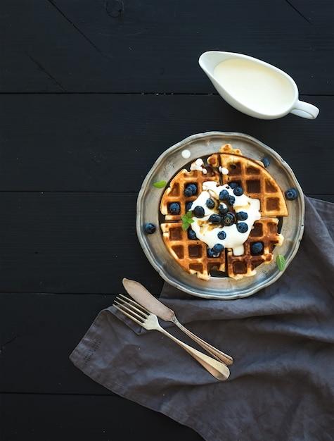 Cialde belghe morbide con mirtilli, miele e panna montata su piastra metallica vintage su sfondo di legno nero, vista dall'alto Foto Premium