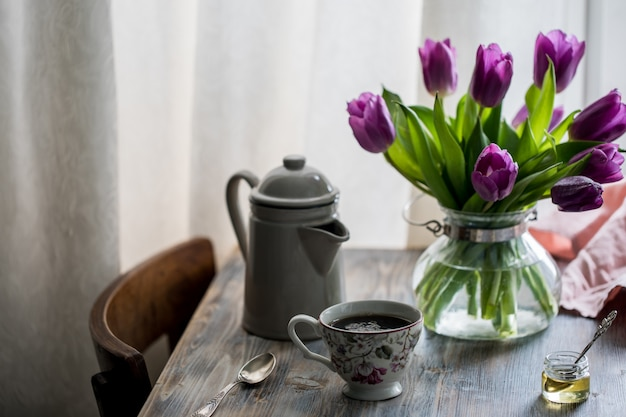Cialde con miele su un tavolo di legno con fiori vicino alla finestra. Foto Premium