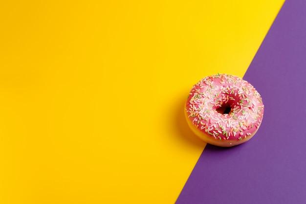 Ciambella rosa sullo spazio rosso-cupo giallo e viola della copia di vista superiore della parete Foto Premium