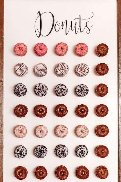 Ciambelle al cioccolato per gli ospiti. festivo. dolci in un giorno di nozze. ciambelle di nozze. un delizioso muro di ciambelle. Foto Premium