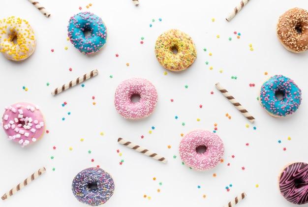 Ciambelle colorate in posizione piatta Foto Gratuite