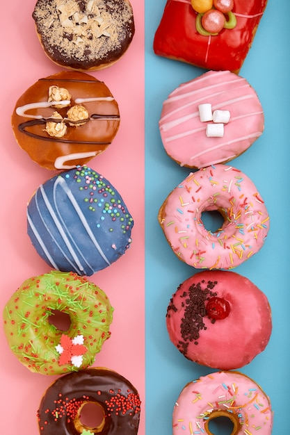 Ciambelle dolci su uno sfondo blu e rosa. ciambelle assortite, colore di sfondo blu rosa sfondo. Foto Premium
