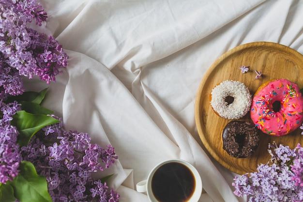 Ciambelle e caffè vicino al lilla Foto Gratuite