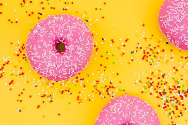 Ciambelle rosa con spruzza colorato su sfondo giallo Foto Gratuite