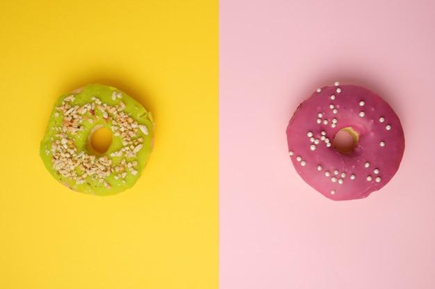 Ciambelle rotonde diverse con sprinkles su uno sfondo multicolore luminoso Foto Premium