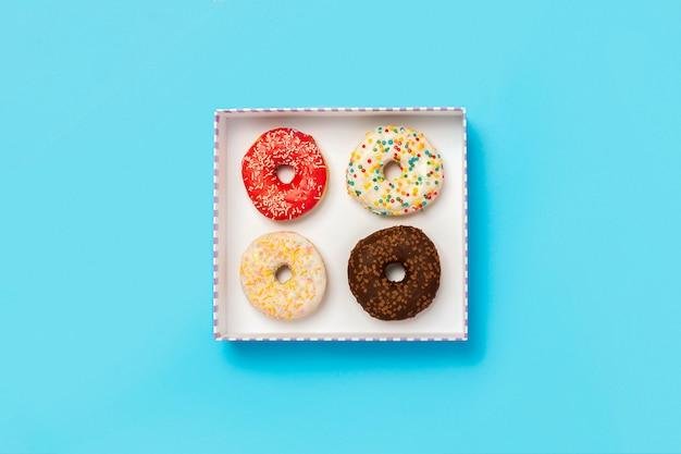 Ciambelle saporite in una scatola su una superficie blu. concetto di dolci, prodotti da forno, pasticcini, caffetteria. . vista piana, vista dall'alto Foto Premium